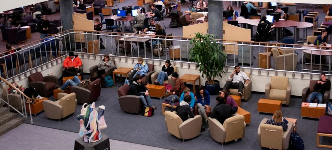 View from above, looking down to the first floor of the library with comfy chairs for studying and socializing.